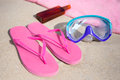 Summer concept flip flops towel diving mask and suntan lotio pink lotion bottle on sandy beach Stock Photo