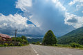 Summer day landscape with forest, cloudy sky and road. Royalty Free Stock Photo