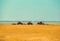 Summer day three tractors to plow, plow the soil on sloping, cornfield. Royalty Free Stock Photo