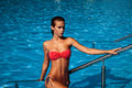 Summer enjoyment young beautiful woman in red bikini in the pool Stock Photos