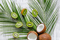 Summer exotic fruits. Kiwi, coconut and palm branch on wooden background top view