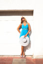 Summer fashion blond woman in blue elegant dress with hat and sunglasses lean on white wall outdoor sunny day Royalty Free Stock Photography