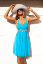 Summer fashion blond woman in blue elegant dress with hat and sunglasses lean on white wall outdoor sunny day Stock Photography