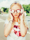 Summer fashion stylish portrait of young pretty sexy blonde girl posing in sunglasses, T-shirt, and listening to music with headph Royalty Free Stock Photo