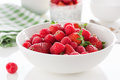 Summer fresh red juicy fruits – raspberries and strawberries in a white bowl on a table for breakfast or lunch Royalty Free Stock Photo