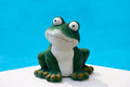 Summer frog a ceramic in front of the the blue water of a swimming pool Stock Photo