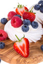 Summer fruit pavlovas pavlova displayed on olive wood board over white background Stock Photos