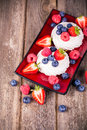 Summer fruit platter on red ceramic plate over old wood background Stock Image