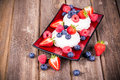 Summer fruit platter on red ceramic plate over old wood background Stock Photography