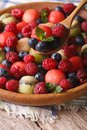 Summer fruit salad in wooden bowl closeup. vertical Royalty Free Stock Photo