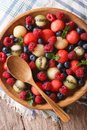Summer fruit salad in wooden bowl closeup. vertical top view Royalty Free Stock Photo