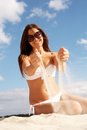 Summer fun portrait of pretty young lady in white bikini playing with sand Royalty Free Stock Photo