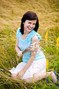 Summer fun pretty girl sitting on grass and dispersing flower seeds happiness Royalty Free Stock Image
