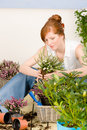 Summer garden terrace redhead woman potted flower Royalty Free Stock Image