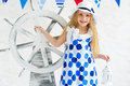 Summer girl in fashion marine style dress adorable spotted and hat standing next to decorative steer wheel Royalty Free Stock Images