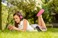 Summer girl lying grass listen music headphones on to pink Stock Photo
