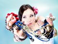 Summer girl plenty of jewellery beads in hands young woman style with blue background Stock Images