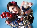 Summer girl plenty of jewellery beads in hands young woman style with blue background Royalty Free Stock Photography