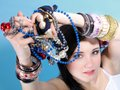 Summer girl plenty of jewellery beads in hands young woman style with blue background Stock Image