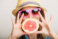 Summer girl tourist holding grapefruit citrus fruit vacation happy in sunglasses and hat on gray healthy food Stock Images