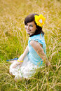 Summer happiness pretty young girl with yellow flower sitting on the meadow Royalty Free Stock Images