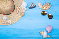 Summer hat, sea shells, sunglasses and  ship on blue background Royalty Free Stock Photo