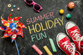 Summer holiday fun poster design childhood toys and red sneakers on black chalkboard from above Stock Photos