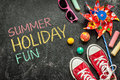 Summer holiday fun poster design childhood toys and red sneakers on black chalkboard from above Stock Image