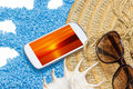 Summer holiday travel concept straw hat sunglasses and a seashell are lying on a little blue stones forming a wave isolated on the Royalty Free Stock Photography
