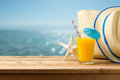Summer holiday vacation concept with orange juice, hat and bag over sea beach Royalty Free Stock Photo