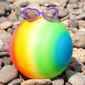 Summer holidays concept rainbow colorful beach ball with sunglasses on the pebbles ready for your text or symbols Royalty Free Stock Photo