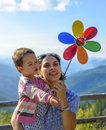 Summer holidays, family, children and people concept - happy mother and child girl with pinwheel toy Royalty Free Stock Photo