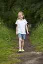 Summer holidays littel girl walking on a path in the woods litte Stock Photos
