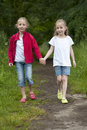 Summer holidays littel girls walking on a path in the woods two little hand hand Royalty Free Stock Image