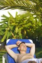 Summer holidays. Young man sunbathing. In the background a palm tree. Vacation concept. Man freelancer lies on a blue lounger. Royalty Free Stock Photo