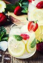 Summer iced lemonade with strawberries, lemon, mint and soda, vi Royalty Free Stock Photo