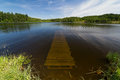 Summer lake wooden pier submerged in natural Royalty Free Stock Photos