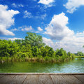 Summer landscape with river blue sky and wood pier Stock Photography