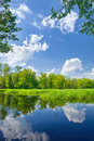 Summer landscape river clouds blue sky green trees Royalty Free Stock Photo