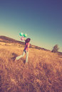 Summer leasure woman in casual clothes run on upland with balloons in hand full body shot day retro colors Stock Photo
