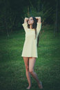 Summer leasure young barefoot woman wearing short retro dress stand barefoot on grass retro colors full body shot Royalty Free Stock Photos