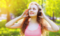 Summer lifestyle portrait young girl with headphones listening music and enjoying nature Royalty Free Stock Photos
