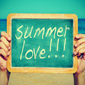 Summer love picture of someone on the beach holding a blackboard with the sentence written on it with a retro effect Royalty Free Stock Photo