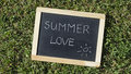 Summer love written on a chalkboard in a park Royalty Free Stock Photos