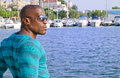Summer marine scene with a handsome black man relaxing and enjoying the summer attractive wearing blouse stripes at sea side Stock Photos