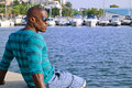 Summer marine scene with a handsome black man relaxing and enjoying the summer attractive wearing blouse stripes at sea side Stock Photography