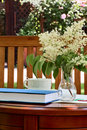 A summer morning on the table in the garden book cup for tea and vase with flowers Stock Photos