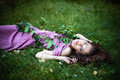 Summer muse beautiful young woman in purple dress lie in green grass day Stock Photo