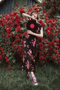 Summer nature background. Fashion brunette model. Spring rose flower garden. Fabulous woman with red lips in dress. Awesome Royalty Free Stock Photo