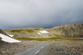 Summer norwegian road asphalt is running past mossy rocks with snowfields this is the to hamningberg highway of the north coast is Stock Images